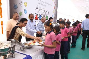 Dignitaries take turns to help serve the food